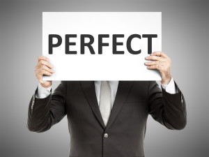 "A man holding a sign saying ""perfect"" in front of his face"