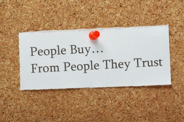 A note pinned on a cork board that says  and quot;People Buy...From People They Trust. and quot;
