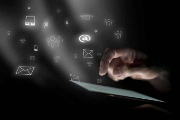 Hand hovering over ipad with social media and email icons hovering in the air.